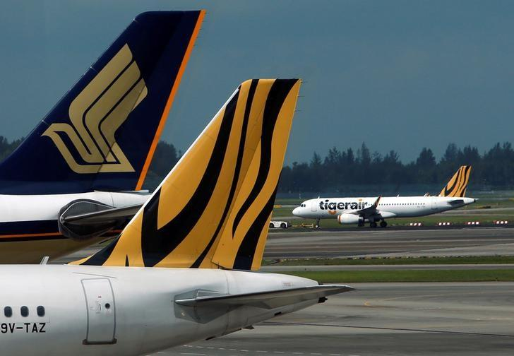 A Tiger Airways plane is towed on the runway past Singapore Airlines and Tiger Airways planes sitting on the tarmac at Changi Airport in Singapore July 21, 2014.  REUTERS/Edgar Su/File Photo