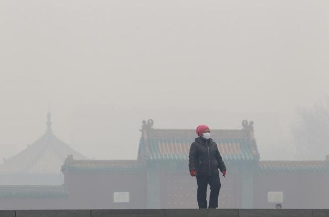 1月12日、中国で2016年、環境保護法に違反し環境を損ねたとして720人が拘束された。写真は大気汚染のなかをマスクをして歩く女性。2015年11月遼寧省で撮影(2017年  ロイター)