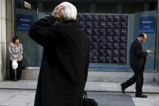 Un hombre mira un tablero electrónico que muestra información de la bolsa de Japón fuera de una correduría en Tokio, Japón. 2 de marzo 2016. El índice Nikkei de la bolsa de Tokio cayó el jueves a un mínimo en casi dos semanas después de que el presidente electo de Estados Unidos, Donald Trump, no logró ofrecer claridad sobre sus futuras políticas fiscales en una rueda de prensa muy esperada.REUTERS/Thomas Peter - RTS8VY3