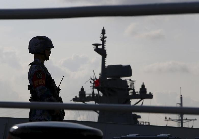A Chinese People's Liberation Army (PLA) navy personnel stands guard on their Jiangkai II class vessel, CNS Yulin, during a display of warships ahead of the IMDEX Asia maritime defence exhibition at Changi Naval Base in Singapore May 18, 2015. REUTERS/Edgar Su