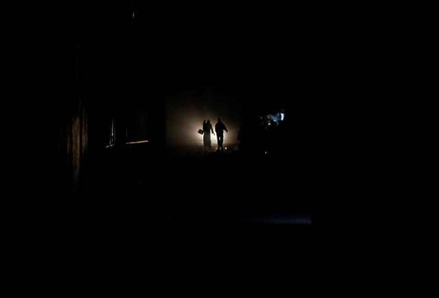 Palestinians walk on a road during a power cut in Beit Lahiya in the northern Gaza Strip January 11, 2017. Picture taken January 11, 2017. REUTERS/Mohammed Salem