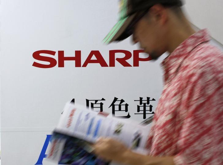 A man walks past Sharp Corp's advertisement board at an electronics store in Tokyo June 8, 2012.REUTERS/Toru Hanai/Files