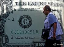 Мужчина проходит мимо изображения американской валюты в Каире 23 ноября 2016 года. Доллар в пятницу отошел от минимума пяти недель к иене и стабилизировался к корзине основных валют, в то время как рынки оставили без внимания не дотянувшие до прогнозов данные о китайском экспорте. REUTERS/Amr Abdallah Dalsh