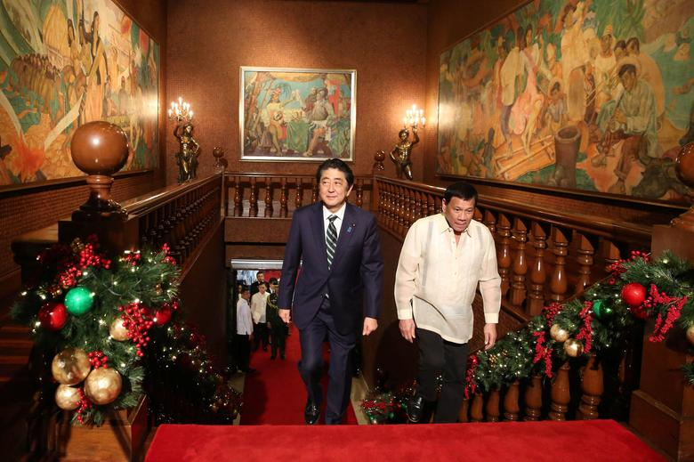 President Rodrigo Duterte (R) walks with Japanese Prime Minister Shinzo Abe as they enter the Malacanang presidential palace in metro Manila, Philippines January 12, 2017. Malacanang Photo/ Handout via Reuters