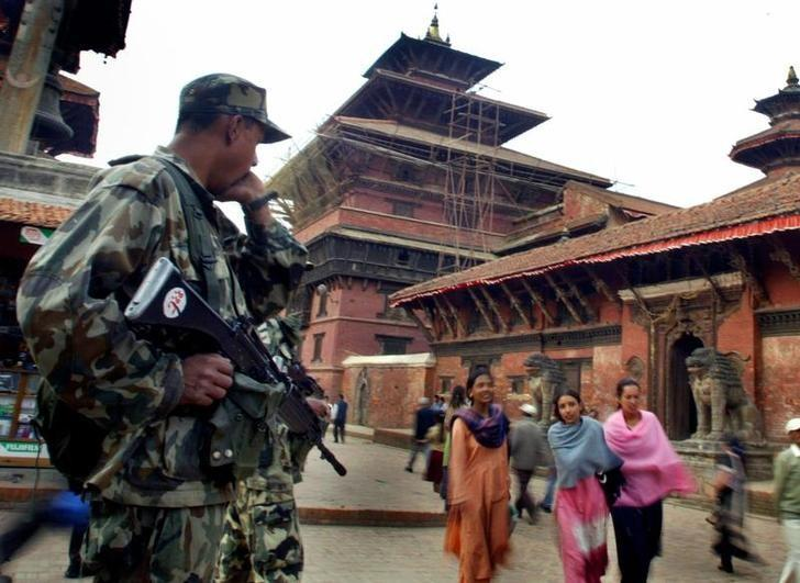 A Nepali army personnel watches on at a protest site in Patan April 6, 2005. REUTERS/Gopal Chitrakar/Files