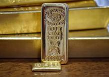 Золотые слитки. Ослабление доллара в пятницу помогло росту цен на золото, которые готовятся завершить в плюсе третью неделю подряд, но рост был ограничен фиксацией прибыли по длинным позициям.   REUTERS/Mariya Gordeyeva