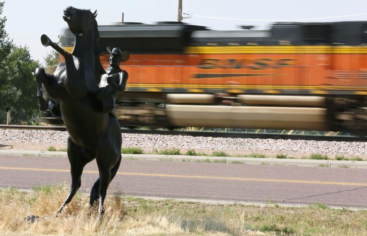 A Burlington Northern Santa Fe (BNSF) train rolls by a statue of the state symbol of the state of Wyoming, a bucking bronco, in Ft. Laramie, Wyoming July 15, 2014.  REUTERS/Rick Wilking