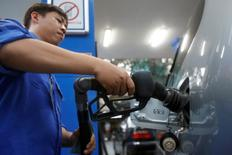 FILE PHOTO: An employee pumps petrol into a car at a petrol station in Hanoi, Vietnam December 20, 2016. REUTERS/Kham/File Photo - RTX2WUNX