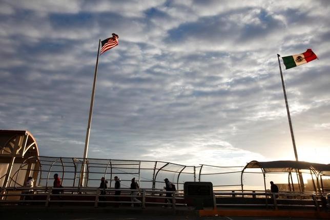 1月16日、トランプ次期米大統領が打ち出す経済政策の柱となりそうなのが国境税だ。具体策はまだ不明だが、民間企業の米国回帰を促すのが目的とみられている。写真はメキシコのシウダー・フアレスから米国のエルパソへ続く国境の橋を渡る人々。昨年12月撮影(2017年 ロイター/Jose Luis Gonzalez)