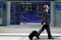 """Un hombre pasa por delante de una tabla electrónica que muestra el promedio del Nikkei fuera de una correduría en Tokio, Japón, 1 de abril 2016.El índice Nikkei de la bolsa de Tokio cayó el lunes a su nivel más bajo en más de dos semanas, luego de que el yen se apreció por las preocupaciones de que Reino Unido pueda sufrir un """"Brexit"""" duro de la Unión Europea. REUTERS/Thomas Peter - RTSD3HP"""