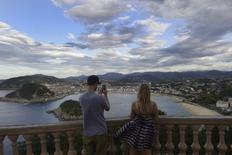 Tras el año récord en 2016, el crecimiento del sector turístico se frenará algo este año por la ralentización del consumo en algunos de sus principales mercados emisores y el menor trasvase de turistas de destinos rivales golpeados el año pasado por una ola de atentados, dijo Exceltur, la patronal de las principales empresas turísticas en España.  En la imagen, dos turistas en un mirador sobre San Sebastián el 19 de septiembre de 2014. REUTERS/Vincent West