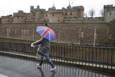 """El Ibex-35 de la bolsa española continuaba el martes a media sesión en terreno negativo, con el ánimo de los inversores dominado por el temor a que Londres opte por un Brexit """"duro"""" cuando la primera ministra británica, Theresa May, detalle a las 11:45 GMT su estrategia de salida de la Unión Europea  En la imagen, un turista con un paraguas de la bandera británica camina bajo la lluvia junto a la Torre de Londres el 15 de enero de 2017.  REUTERS/Peter Nicholls"""