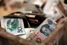 En la imagen, billetes chinos en la caja de cambio de un vendedor en un mercado de Pekín, el 14 de febrero de 2014. Los costos del financiamiento a corto plazo en China se dispararon el jueves a máximos de casi 10 años por temor a una escasez de efectivo antes de la principal celebración del año, pero cerraron lejos del techo de sesión porque los bancos estatales intervinieron con una mayor oferta de yuanes.    REUTERS/Kim Kyung-Hoon/File Photo