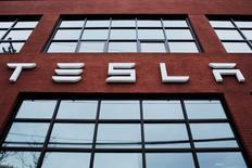 FILE PHOTO: A Tesla logo hangs on a building outside of a Tesla dealership in New York, U.S., April 29, 2016. REUTERS/Lucas Jackson/File Photo