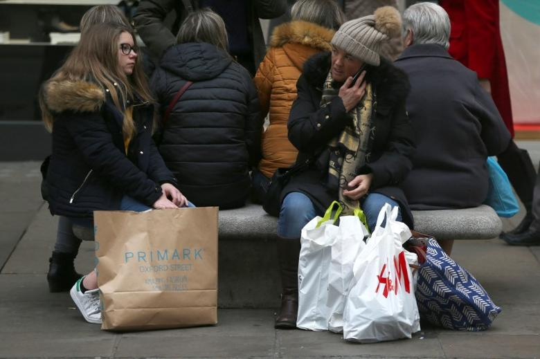 FILE PHOTO -  Shoppers rest on a bench with their bags on Oxford Street in London, Britain December 18, 2016. REUTERS/Neil Hall/File Photo