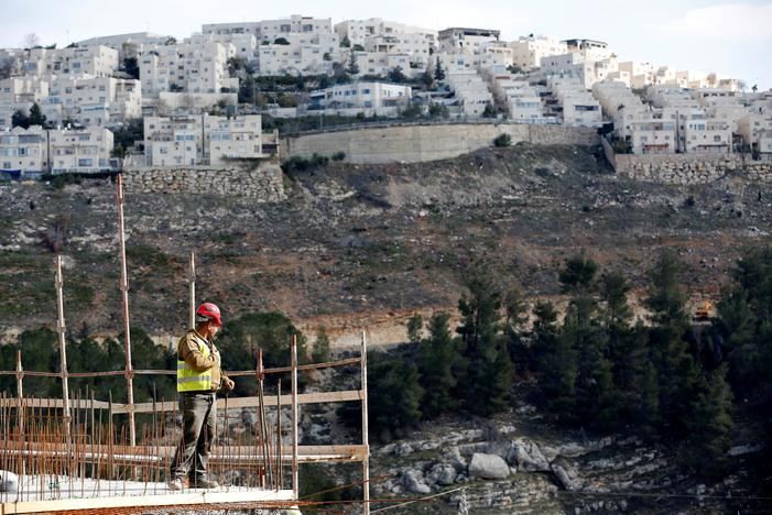 A labourer works at a construction site in the Israeli settlement of Ramot, as the Israeli settlement of Ramat Shlomo is seen in the background, in an area of the occupied West Bank that Israel annexed to Jerusalem January 22, 2017. REUTERS/Ronen Zvulun