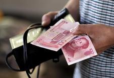 Un cliente sostiene un billete de 100 yuanes en un mercado de Pekín, China.12 de agosto 2015.China registró un déficit fiscal significativamente mayor que su objetivo en 2016, según un cálculo de Reuters basado en datos preliminares publicados el lunes por el Ministerio de Finanzas. REUTERS/Jason Lee