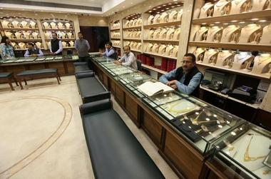 Salespersons wait for customers at a gold jewelry showroom in Chandigarh