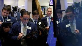 Трейдеры на торгах Нью-Йоркской фондовой биржи 23 января 2017 года. Американский фондовой рынок завершил торги понедельника снижением основных индексов, поскольку первые шаги Дональда Трампа на посту президента США показали его приверженность протекционистской политике, дав инвесторам повод переосмыслить послевыборное ралли. REUTERS/Brendan McDermid