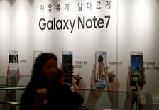 A woman talking on her mobile phone walks past an advertisement promoting Samsung Electronics' Galaxy Note 7 at company's headquarters in Seoul, South Korea, October 11, 2016.   REUTERS/Kim Hong-Ji/File Photo - RTSS08V