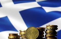 En la imagen, monedas de euro delante de una bandera de Grecia, el 29 de junio de 2015.Grecia superó sus objetivos fiscales el año pasado y probablemente logre cumplir los de este año, situándose en el buen camino para conseguir su primer superávit primario en 2018, dijo el vicepresidente de la Comisión Europea, Valdis Dombrovskis. REUTERS/Dado Ruvic/File Photo