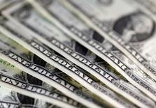 Долларовые купюры 7 ноября 2016 года. Доллар вернулся к росту в пятницу, отойдя от минимума семи недель, на фоне оптимизма в отношении прогноза экономики США и корпоративной отчётности, в то время как мексиканский песо снизился после того, как Белый дом предложил ввести 20-процентную пошлину на мексиканские товары для финансирования строительства стены на границе двух стран. REUTERS/Dado Ruvic/Illustration