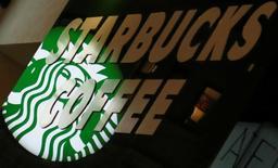 Логотип Starbucks на заведении компании в Вене. Starbucks Corp в четверг ухудшила годовой прогноз выручки и отчиталась о меньшем, чем ожидалось, росте квартальных продаж в ресторанах в Северной и Южной Америке. REUTERS/Leonhard Foeger