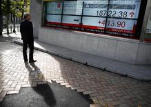 Un hombre mira un tablero electrónico que muestra el promedio Nikkei de Japón fuera de una correduría en Tokio, 1 de diciembre 2016. El índice Nikkei de la bolsa de Tokio subió el viernes luego de que la confianza fue apoyada por la fortaleza del dólar frente al yen, pero las ganancias fueron limitadas por la inquietud sobre las políticas proteccionistas del presidente estadounidense, Donald Trump. REUTERS/Kim Kyung-Hoon