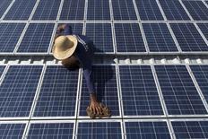 Homem limpa painéis solares que fornecem energia para máquina de fazer gelo na comunidade de Vila Nova do Amana, no Amazonas 22/09/2015. REUTERS/Bruno Kelly