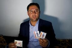 Botan Mahmoud Hassour muestra su tarjeta de identidad de cuando trabajaba para el Ejército de Estados Unidos, mientras espera por una fecha para viajar al país norteamericano tras la decisión del Gobierno de Donald Trump de imponer restricciones de ingreso  a ciudadanos de siete naciones, incluyendo su natal Irak. REUTERS/Ahmed Saad