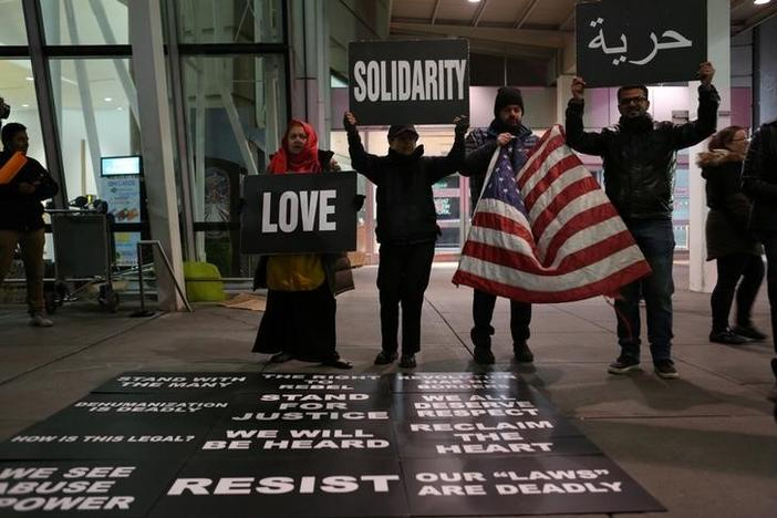 Protesters hold signs in opposition to U.S. President Donald Trump's ban on immigration and travel outside Terminal 4 at JFK airport in Queens, New York City, New York, U.S. January 29, 2017. REUTERS/Joe Penney