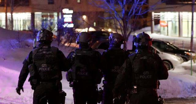 Swat team police officer walk aournd a mosque after a shooting in Quebec City, January 29, 2017. REUTERS/Mathieu Belanger