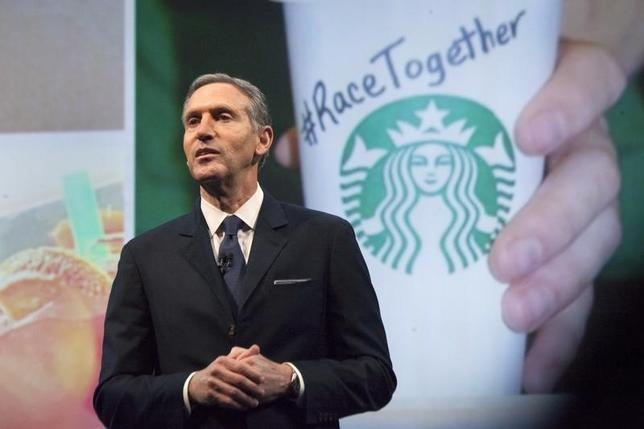 Starbucks Corp Chief Executive Howard Schultz, pictured with images from the company's new ''Race Together'' project behind him, speaks during the company's annual shareholder's meeting in Seattle, Washington March 18, 2015.   REUTERS/David Ryder