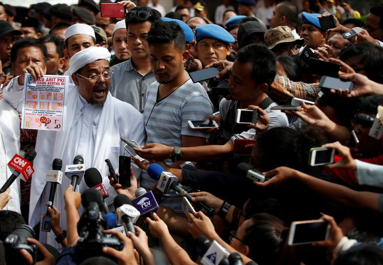 The leader of the hardline Islamic Defenders Front (FPI), Habib Rizieq, speaks to journalists at police headquarters following his questioning by police over his claims that new bank notes contain symbols resembling the Communist hammer and sickle, which are illegal, in Jakarta, Indonesia January 23, 2017. REUTERS/Darren Whiteside