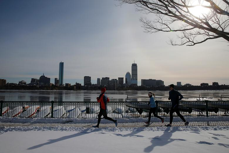 Joggers run along the Charles River past the Boston skyline on a sunny winter's day in Cambridge, Massachusetts. REUTERS/Brian Snyder