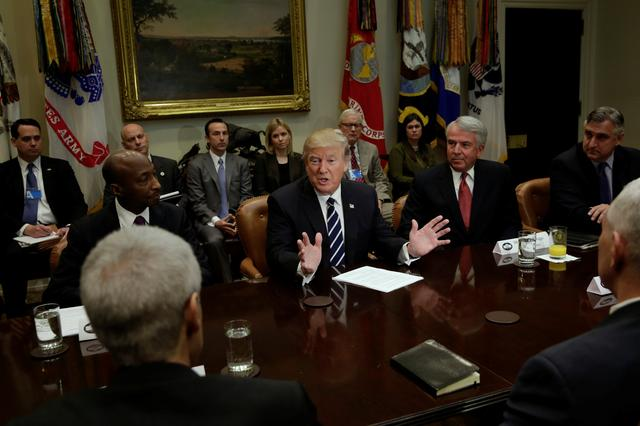 U.S. President Donald Trump, flanked by Kenneth Frazier (L) CEO of Merck, Robert Hugin (2nd R) Executive Chairman of Celgene and Robert Bradway (R) CEO of Amgen meets with Pharma industry representatives at the White House in Washington, U.S., January 31, 2017. REUTERS/Yuri Gripas