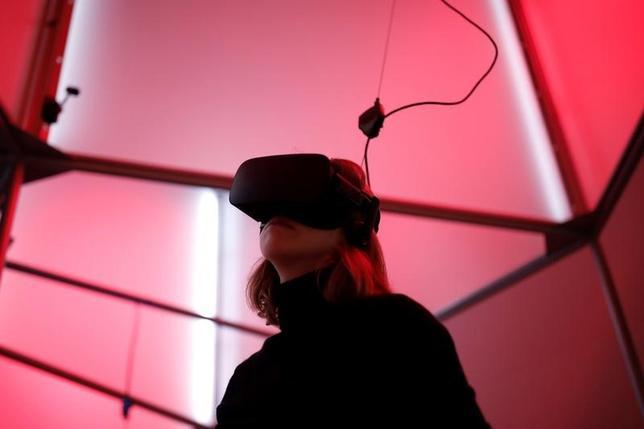 2月1日、米テキサス州ダラスの連邦陪審は、フェイスブックや傘下の仮想現実(VR)機器メーカーのオキュラスなどに対して、5億ドルをゲーム開発会社ゼニマックス・メディアに支払うよう命じた。写真はオキュラスリフトVRヘッドセットでビデオゲームに興じる女性。パリにあるバーチャルリアリティ専門店で昨年12月撮影(2017年 ロイター/Benoit Tessier)