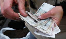 Продавец в Красноярские пересчитывает рублевые купюры. Рубль в небольшом плюсе к доллару утром четверга, и на его стороне выступает отрицательная динамика валюты США на мировых рынках после комментариев ФРС, а также существенно подорожавшая накануне нефть, против - ожидания негативного эффекта от покупок валюты Центробанком по поручению Минфина, которые начнутся на следующей неделе. REUTERS/Ilya Naymushin