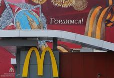Логотип McDonald's на фоне граффити, посвященного победе СССР во Второй мировой войне, в Москве 17 августа 2016 года. Открытие первого в России ресторана американской сети фастфуда McDonald's в Москве в 1990-м, ознаменовавшееся многотысячными очередями, стало одним из признаков медового месяца в отношениях двух стран после окончания холодной войны. REUTERS/Sergei Karpukhin