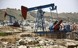 Станки-качалки в Баку 16 июня 2015 года. Цены на нефть сохранили положительную динамику на торгах в четверг благодаря сокращению добычи ОПЕК и странами вне картеля.  REUTERS/Kai Pfaffenbach