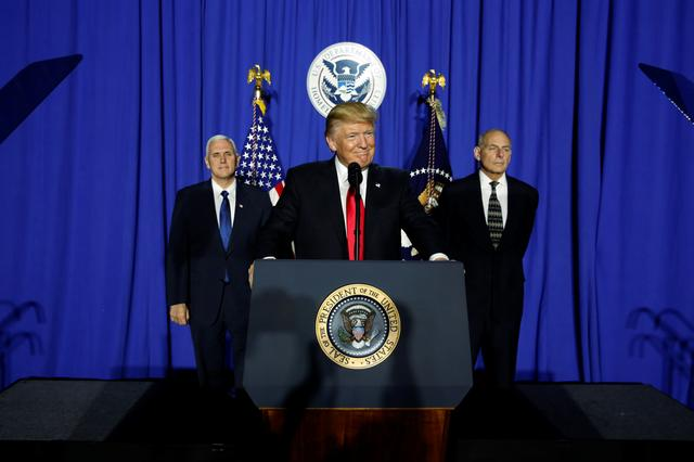President Trump, flanked by Vice President Mike Pence and Homeland Security Secretary John Kelly, at the Homeland Security headquarters.  REUTERS/Jonathan Ernst