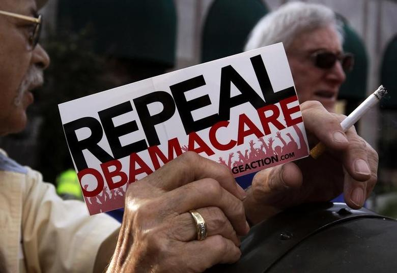 A small group of demonstrators stand outside of of a hotel before former South Carolina Senator Jim DeMint, president of the The Heritage Foundation, speaks at a ''Defund Obamacare Tour'' rally in Indianapolis, Indiana, U.S.  August 26, 2013.  REUTERS/Nate Chute/File Photo