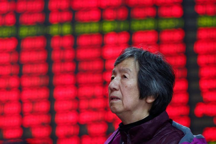 An investor looks at an electronic board showing stock information on the first trading day after the New Year holiday at a brokerage house in Shanghai, China, January 3, 2017.  REUTERS/Aly Song