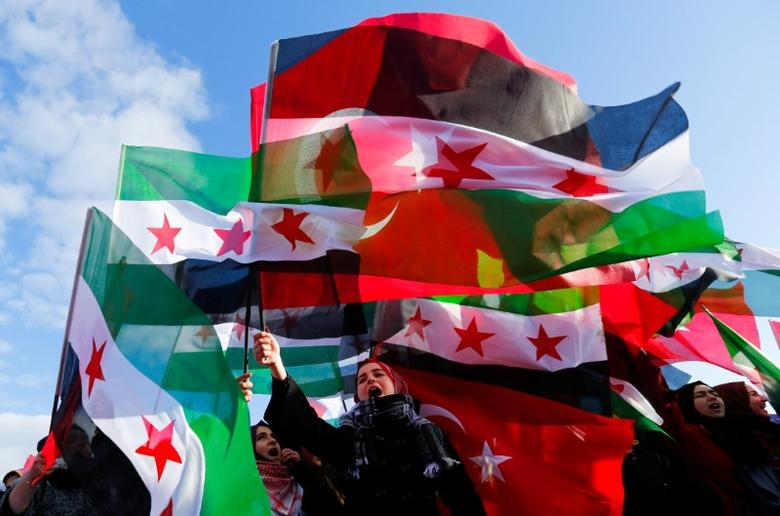 People wave Turkish and Free Syrian Army flags during a gathering before the departure of a Syria-bound aid convoy, carrying humanitarian supplies, in Istanbul, Turkey, December 14, 2016. REUTERS/Murad Sezer/Files