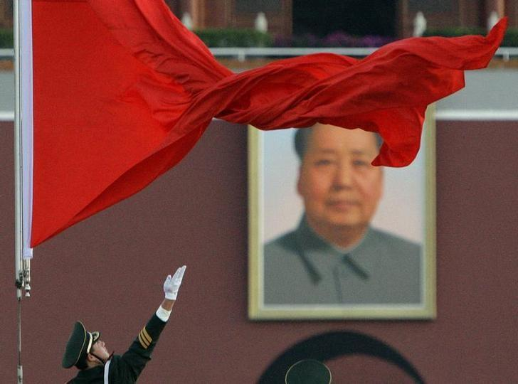A soldier unfurls the Chinese national flag as it is raised in front of the giant portrait of Chairman Mao Zedong in Beijing's Tiananmen Square October 15, 2007. REUTERS/David Gray/Files