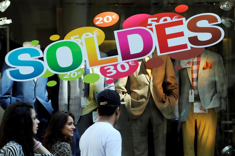 FILE PHOTO:  People walk past a shop with a sale sign on display in Brussels, Belgium, July 2, 2014.       REUTERS/Eric Vidal/File Photo