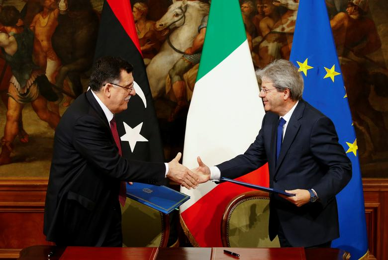 Italian Prime Minister Paolo Gentiloni (R) and his Libyan counterpart Fayez al-Sarraj shake hands after signing a bilateral agreement during a meeting at Chigi Palace in Rome, Italy February 2, 2017. REUTERS/Tony Gentile