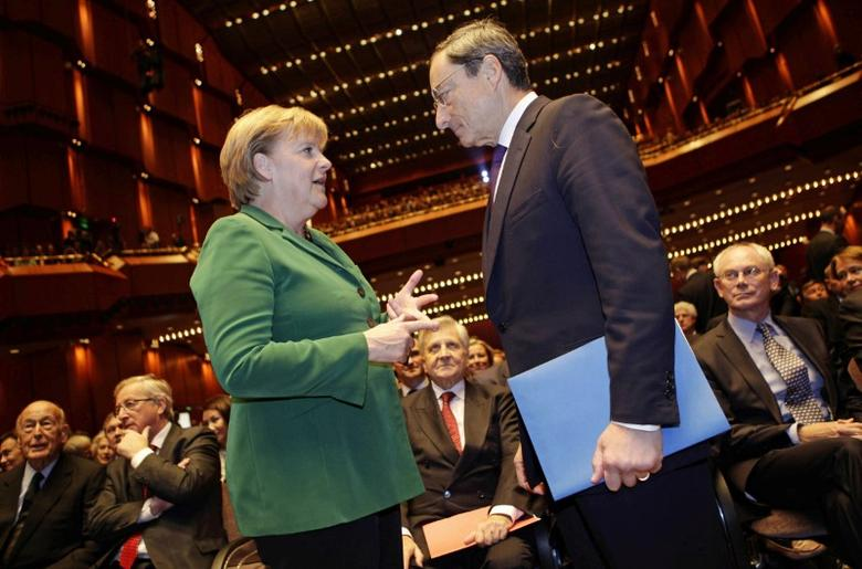 FILE PHOT: German Chancellor Angela Merkel (L) talks to new European Central Bank (ECB) President Mario Draghi prior to a farewell ceremony for outgoing ECB President Jean-Claude Trichet at the old opera house in Frankfurt, October 19, 2011. REUTERS/Kai Pfaffenbach /File Photo