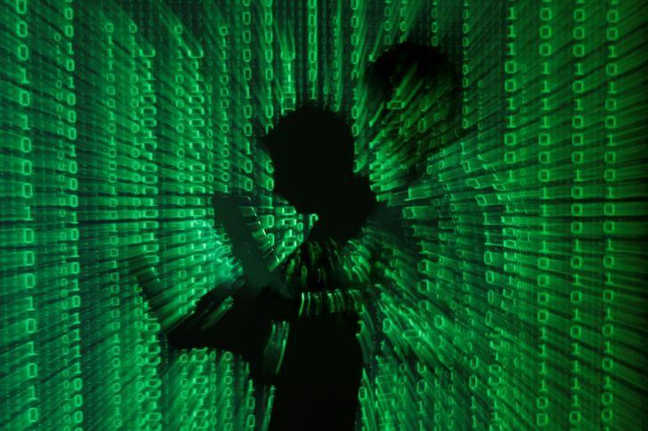 An illustration picture shows a projection of binary code on a man holding a laptop computer, in an office in Warsaw June 24, 2013. REUTERS/Kacper Pempel/Illustration/Files