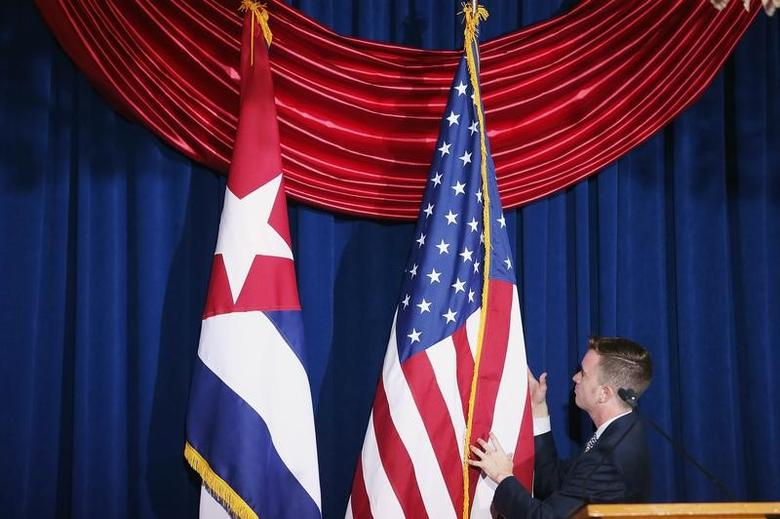 Cuban and American flags are straightened during the re-opening ceremony for the Cuban embassy in Washington July 20, 2015. REUTERS/Chip Somodevilla/Pool